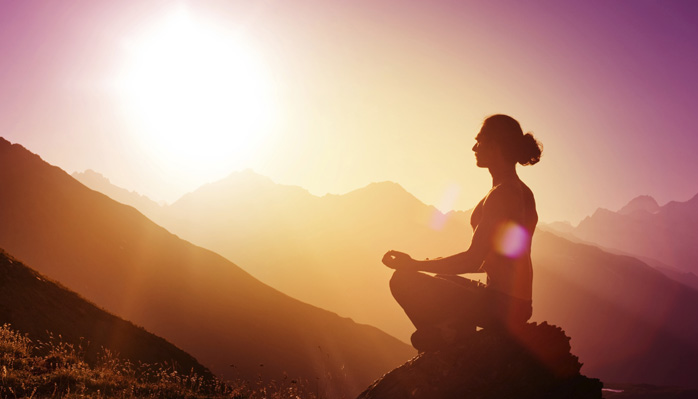 woman meditating outside sunrise
